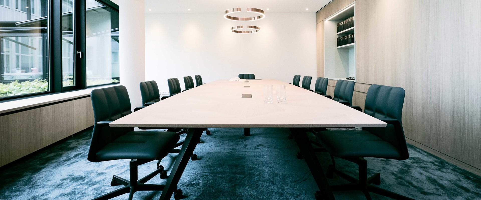 Bild zeigt einen großzügigen Konferenztisch in einem modernen Raum